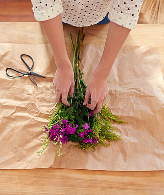 Buy stock photo Cropped shot of a young woman arranging flowers at home