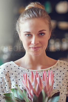 Buy stock photo Closeup portrait of a beautiful young woman holding a protea flower indoors