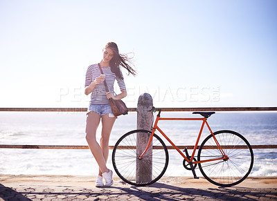 Buy stock photo Shot of a woman texting with her bicycle next to her