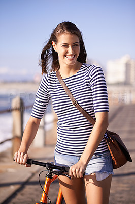 Buy stock photo Shot of an attractive young woman cycling