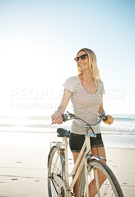 Buy stock photo An attractive young woman riding her bicycle on the beach