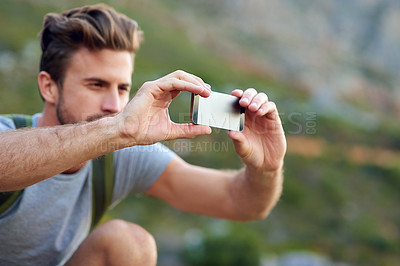 Buy stock photo Shot of a handsome young man snapping pics while hiking