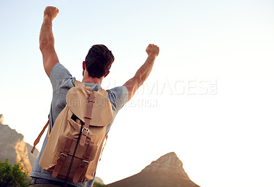 Buy stock photo Shot of a handsome young man standing with his arms raised while hiking