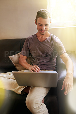 Buy stock photo Shot of a handsome young man using a laptop on the sofa at home