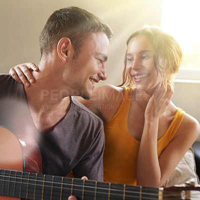 Buy stock photo Shot of a young man playing the guitar while relaxing on the sofa with his wife