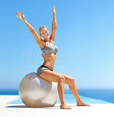 Buy stock photo Portrait of an attractive young woman working out with an exercise ball by a swimming pool