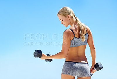 Buy stock photo Rearview shot of young woman exercising with dumbbells outside
