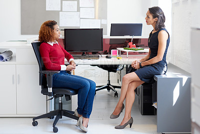 Buy stock photo Shot of two female colleagues talking at a desk in an office