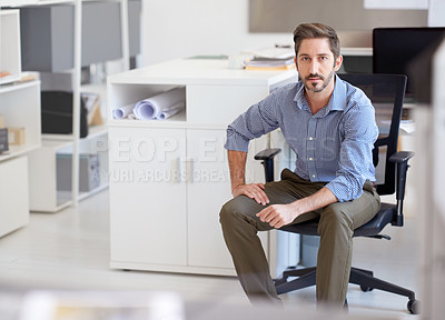 Buy stock photo Portrait of a young designer sitting at his workstation in an office