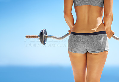 Buy stock photo Rearview shot of a young woman lifting weights outside