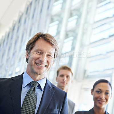 Buy stock photo Portrait of a mature businessman with his colleagues standing in the background