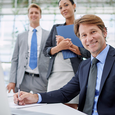 Buy stock photo Portrait of a mature businessman with his colleagues standing behind him
