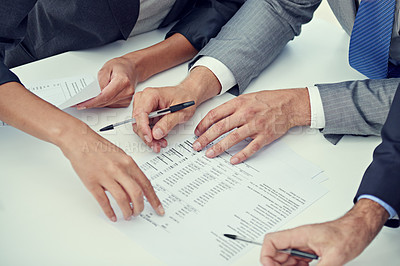 Buy stock photo Cropped shot of a group of businesspeople reviewing financial documents