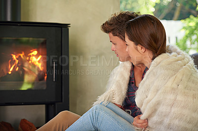 Buy stock photo Shot of an affectionate couple sitting by the fireplace in their living room