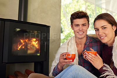 Buy stock photo Shot of a young couple drinking hot chocolate by the fireplace