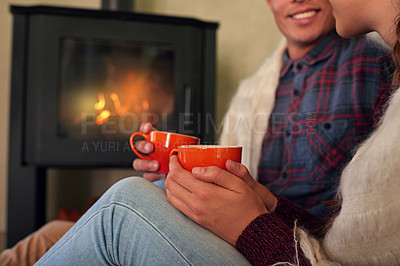 Buy stock photo Cropped shot of a young couple drinking hot chocolate by the fireplace