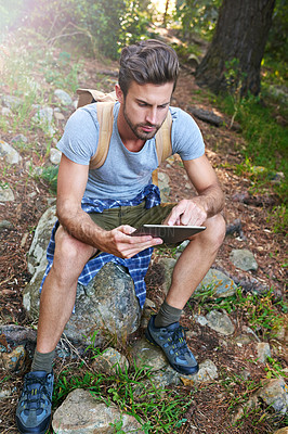 Buy stock photo Shot of a hiker using his digital tablet