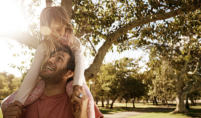 Buy stock photo Shot of a father giving his daughter a piggyback ride at the park