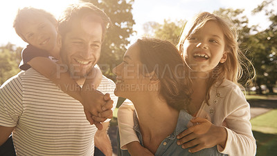 Buy stock photo Shot of two parents giving their children piggyback rides at the park