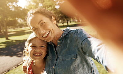 Buy stock photo A mother and daughter taking a selfie while at the park