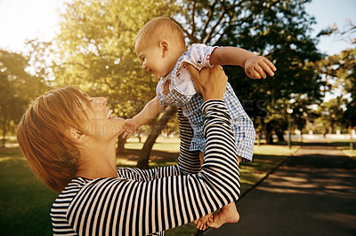 Buy stock photo Shot of a mother holding her baby outside