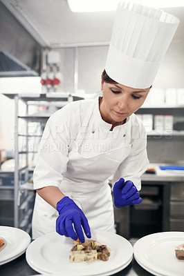 Buy stock photo Shot of a chef plating food for a meal service in a professional kitchen