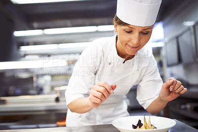 Buy stock photo Shot of a chef preparing dessert in a professional kitchen