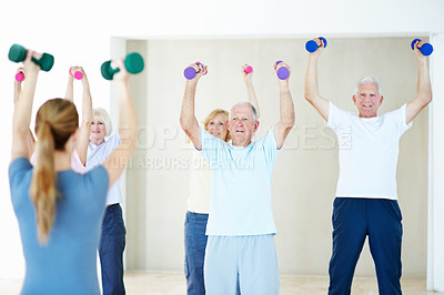 Buy stock photo A group of elderly people standing and lifting weights together