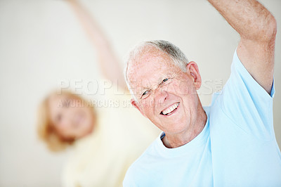 Buy stock photo An elderly man doing stretches in a group yoga class