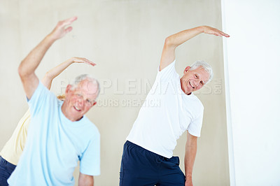 Buy stock photo Two elderly men doing stretches in a class with a senior woman in the background
