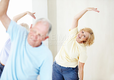 Buy stock photo An elderly woman doing stretches in a group class with a senior man in the foreground