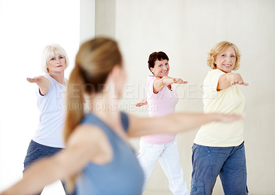 Buy stock photo A group of elderly woman doing some arm stretches in a group gym class
