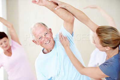 Buy stock photo Portrait of an elderly man doing stretches and being assisted by a young instructor