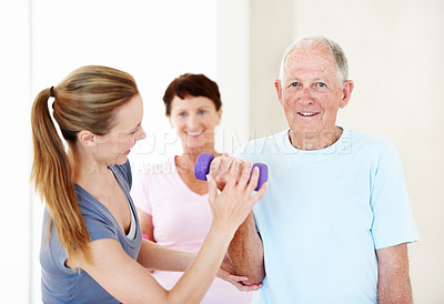 Buy stock photo An elderly man being helped with his weights by the gym instructor