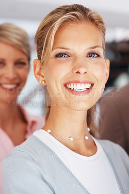 Buy stock photo Pretty young businesswoman standing confidently with colleagues in background