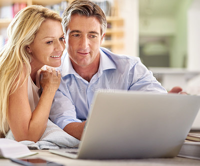 Buy stock photo Shot of a mature couple lying on their living room floor doing some online research