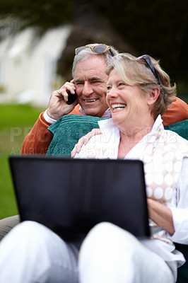 Buy stock photo Shot of a senior couple using a laptop and cellphone while on vacation