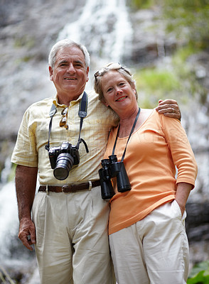 Buy stock photo Portrait of a loving senior couple with binoculars and a camera exploring nature together