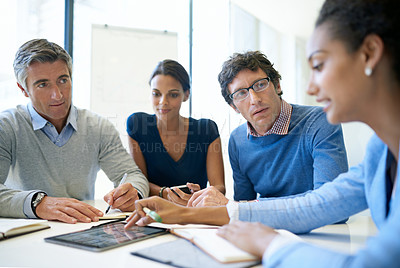 Buy stock photo A group of businesspeople discussing work using a digital tablet in a boardroom meeting