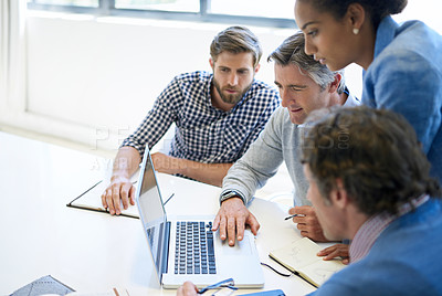 Buy stock photo A group of business colleagues discussing work on a laptop during a boardroom meeting