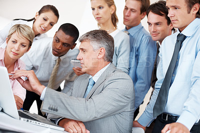 Buy stock photo Senior manager pointing in the laptop to his colleagues standing behind - Group discussion