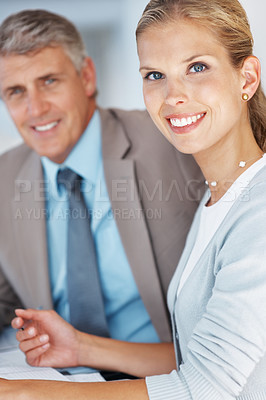 Buy stock photo Portrait of a happy business man and woman sitting together by the desk in office