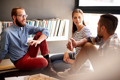 Buy stock photo Shot of designers having pizza while working together on a creative project