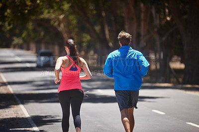 Buy stock photo Rearview shot of a couple jogging on a road
