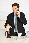 Happy executive using cellphone while drinking coffee at home