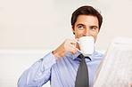 Young executive drinking coffee while looking away
