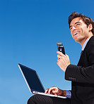 business man using a laptop while holding a mobile phone
