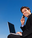 Executive using a laptop and cellphone against blue sky