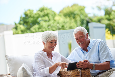 Buy stock photo Shot of a senior couple using a tablet while sitting on their patio9