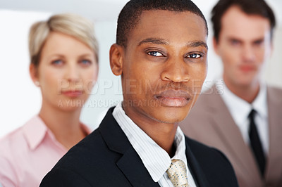 Buy stock photo Smart young african american businessman looking confidently and his colleagues standing behind at office